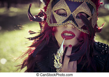 beautiful woman with full lips and Venetian mask at sunset