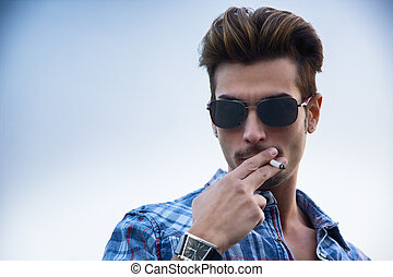 Trendy cool young man standing outside smoking