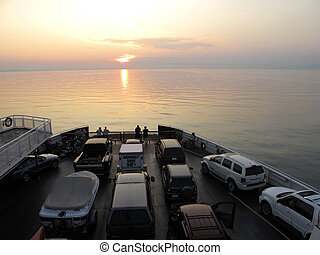 ferry with cars and people sailing into the sunset