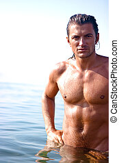 Muscular man standing in the sea water
