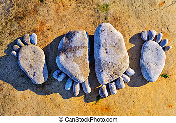 Four stone footprints in the sandy beach