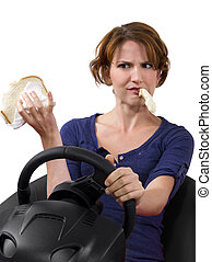 Eating While Driving - female driver eating a sandwich while...