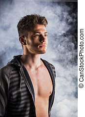 Handsome tough young man in dark hoodie on smoky background...