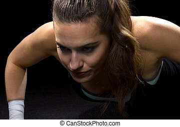 Pushups - fit woman doing pushups on black background