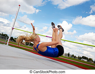 High Jump - A young, athlete clearing the bar during a high...