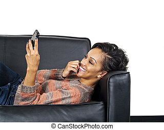 Relaxing and Texting - woman laying on a couch and reading...