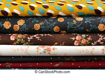 heap of cloth fabrics on wooden table