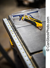 Protective Glasses and Utility Knife on a Table Saw