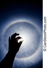 Hand silhouette with Circular Sun Halo in Background