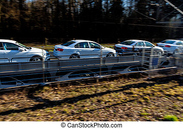new car on a freight train - a freight train brings new cars...