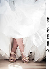 Crossed legs of a Bride Wearing her Wedding Shoes