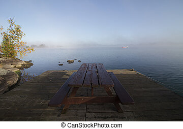 Picnic Table with No People on a Dock During a Foggy Calm...