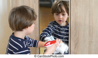 Boy Cleaning the Mirror - Cute boy cleaning the mirror using...