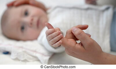 Baby holding mother's finger at home