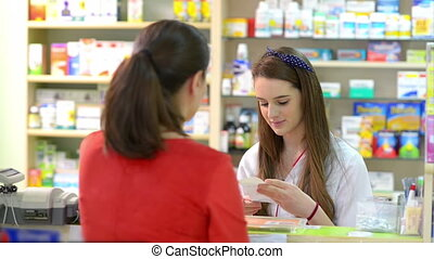 Customer in a drugstore buying some - Young female...