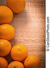 frame of orange fruits on wooden board with organized copyspace