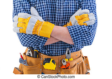 crossed arms of construction worker and tools in toolbelt...