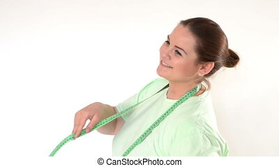 Corpulent woman wrapping a measuring tape around the neck...