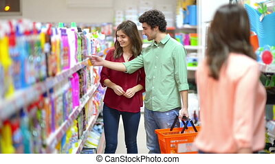 Customers choosing cleaning product - Happy woman showing to...