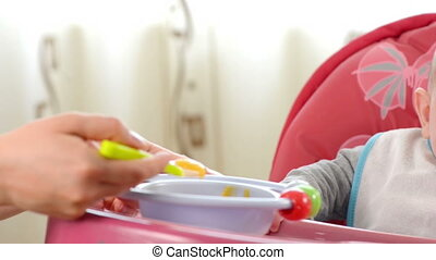 Baby eating in a high chair - Baby boy eating in a high...