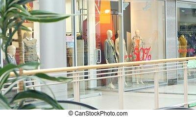 Blonde walks around the glass shop windows