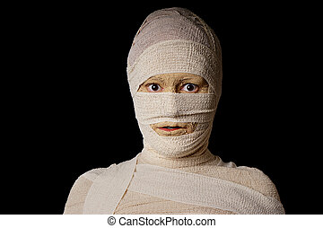 wide eyed egyptian mummy - woman wrapped up with bandages as...