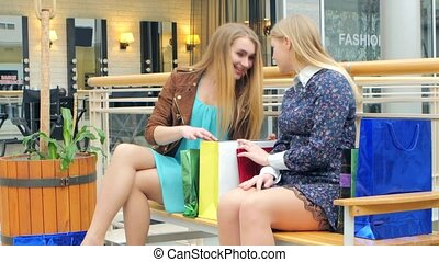 Two blondes sitting on a bench talking, bragging about their purchases