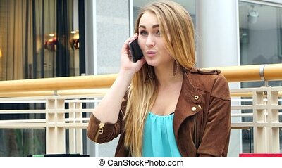 Blonde talking phone at the mall sitting on bench