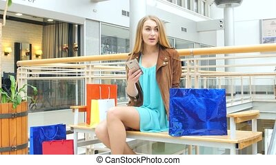 Beautiful blonde sitting on a bench Mall - Two beautiful...