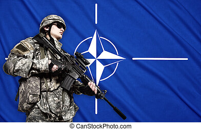 soldier on NATO flag background - soldier holding rifle on a...