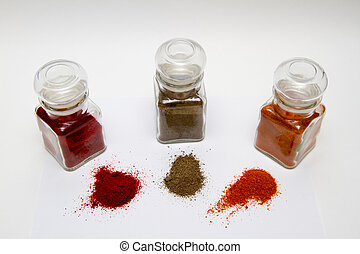 glass spice jars with different kinds of pepper