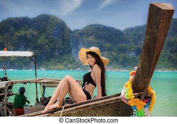 Maya bay - Asian lady take holiday in wooded boat in Maya...