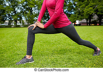 close up of woman stretching leg outdoors - fitness, sport,...
