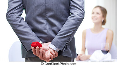 close up of man hiding red box behind from woman - couple,...