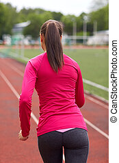 woman running on track outdoors from back - fitness, sport,...
