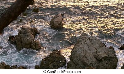 Golden Seawater on the Rocks - Golden sun light over the...