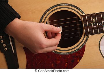 Guitar Strumming - Hand holding a plectrum and strumming...
