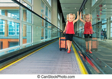 Joyful girl with her trunk on airport moving walkway - Blond...