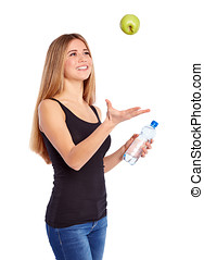 Girl with green apple and pet bottle full of water on a...