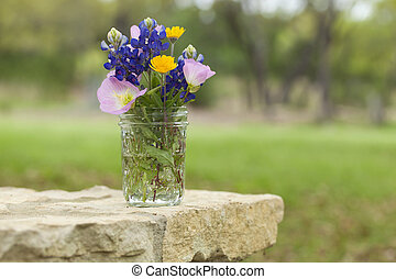 Bouquet of Texas wildflowers in a jar on stone wall - A...
