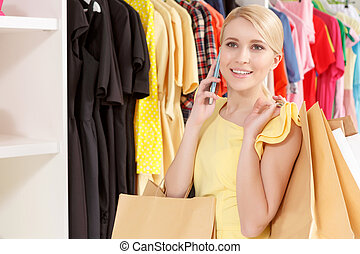 Young shopper speaks over the phone - Friendly chat....