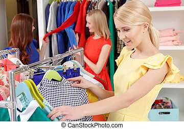 Woman chooses clothes in a store - Hard choice. Young...