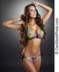 Long-haired brunette touts fashionable swimsuit - Image of...