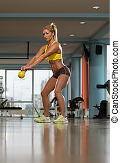Attractive Female Doing Kettle Bell Exercise - Middle Age...