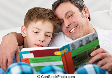 Son and father reading book together - Father and son...