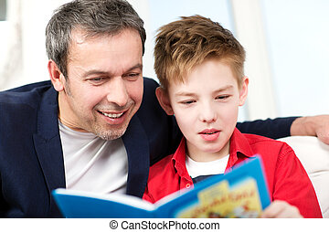 Dad and son reading a book at home - Happy father and son...