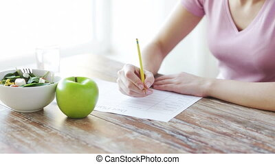 close up of young woman writing diet plan at home - healthy...