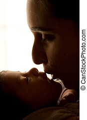 silhouette of mother and baby - a mother kissing her new...