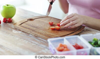 close up of woman chopping vegetables at home - healthy...
