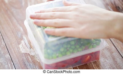 close up of woman opening box with vegetables - food,...